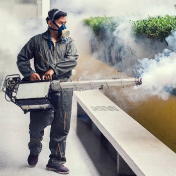 Дезинсектор распыляет средство для борьбы с тараканами с помощью горячего тумана